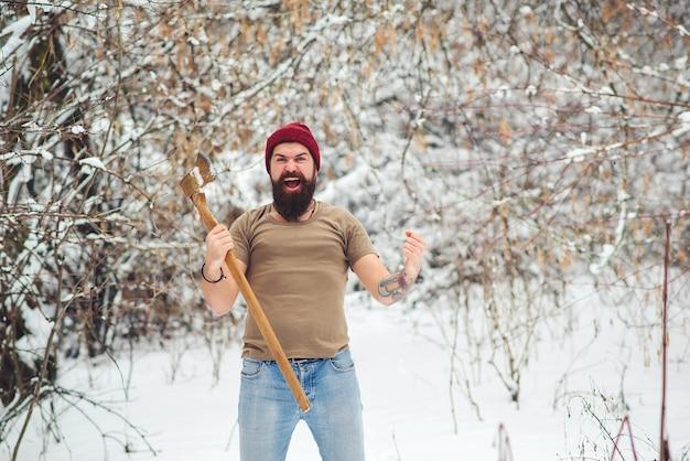雪に覆われた森のひげを生やした木こり。冬の公園で斧で残忍なひげを生やした男。