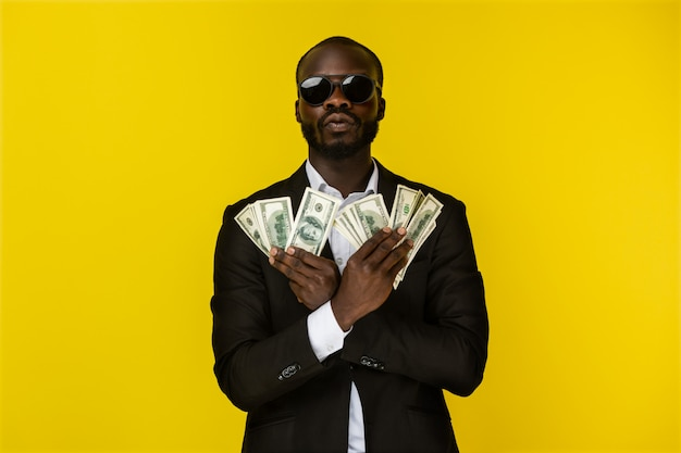 Bearded luxury young afroamerican guy is holding lots of money in both hands in sunglasses and black suit