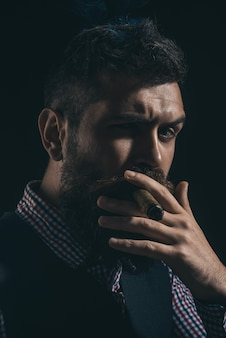 Bearded macho with cigar. gentleman in checkered shirt and waistcoat smoking cigar. elegant man with beard, mustache smoke cigar. classical vintage male portrait. bearded man in stylish retro clothes.