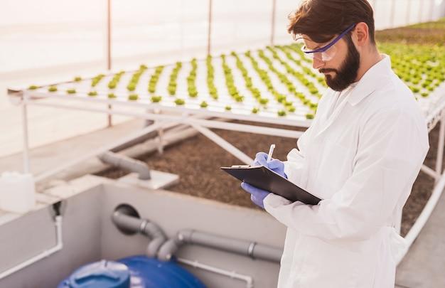 실험실 코트에 수염 난 남성 농업 경제학자와 온실의 수경 재배 테이블 근처에 서있는 동안 클립 보드에 쓰는 고글