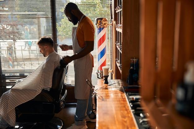 金属バリカンでクライアントの髪を切るひげを生やした男性の床屋