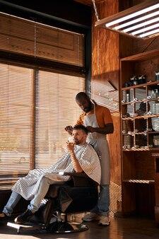 はさみでクライアントの髪を切るひげを生やした男性の床屋