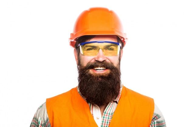 Бородатый мужчина-строитель в каске и очках.