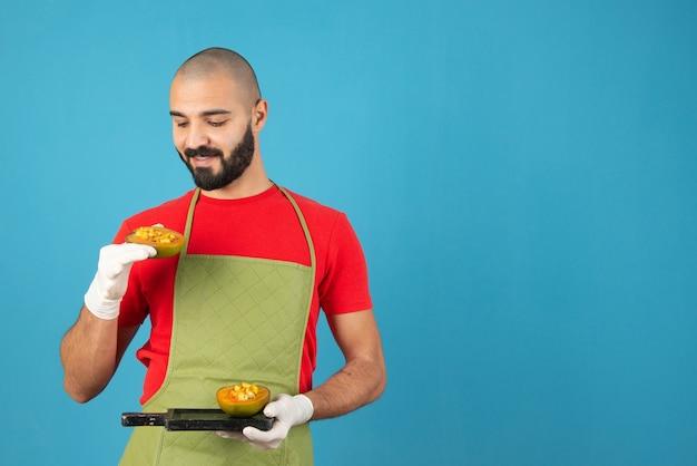 앞치마와 장갑에 수염난 남성 요리사가 패스트리와 함께 어두운 나무 판자를 들고 있습니다.