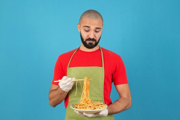 おいしいスパゲッティのプレートを保持しているエプロンと手袋のひげを生やした男性シェフ。