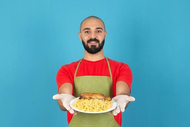 Бородатый шеф-повар-мужчина в фартуке и перчатках держит белую тарелку вкусной пасты с куриным мясом.