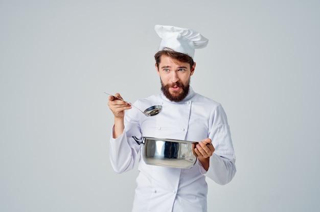Бородатый мужчина-шеф-повар с кастрюлей в руках готовит еду на кухне