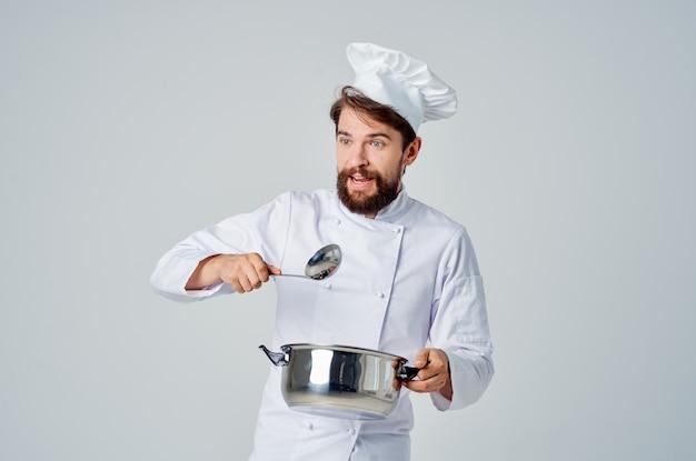 手に鍋を持ったひげを生やした男性シェフ料理キッチンの専門家
