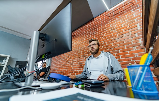 Bearded male computer programmer in glasses develops new technologies at his workplace.