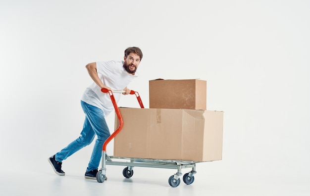 Bearded male courier with cardboard boxes on a cargo trolley