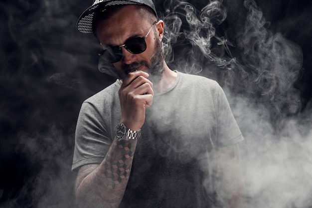 Bearded male dressed in a grey shirt, sunglasses and baseball cap vaping