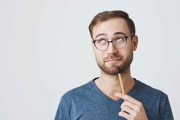 Bearded male employee in glasses, holding pencil, look away pondering
