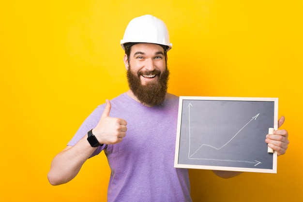 수염난 남성 엔지니어는 엄지손가락을 들고 그래픽이 있는 칠판을 들고 단단한 모자를 쓰고 있습니다.