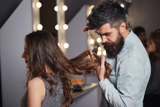 Бородатый мужчина-парикмахер стригет клиентам волосы ножницами в парикмахерской