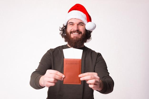 ひげを生やした男性のヒップスターがパスポートに2枚の航空券を提示しています。