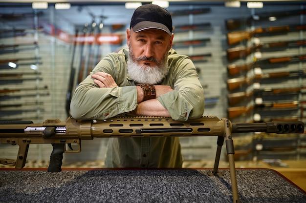 Бородатый мужчина-охотник за прилавком с мощной винтовкой в оружейном магазине. интерьер оружейного магазина, ассортимент боеприпасов и боеприпасов, выбор огнестрельного оружия, хобби и образ жизни.