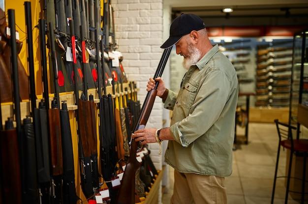 총기 가게에 사냥용 소총이 줄지어 있는 쇼케이스의 수염난 남성 사냥꾼. 무기 상점 인테리어, 탄약 및 탄약 구색, 총기 선택, 사격 취미 및 라이프 스타일