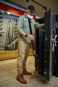 수염을 기른 남성 사냥꾼이 상점에서 사냥용 소총용 총 보관함을 구입합니다. 무기 상점 인테리어, 탄약 및 탄약 구색, 총기 선택, 사격 취미 및 라이프 스타일
