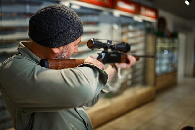 총기 가게에서 광학 시력으로 사냥용 소총을 사는 수염 난 남성 사냥꾼. 무기 상점 인테리어, 탄약 및 탄약 구색, 총기 선택, 사격 취미 및 라이프 스타일