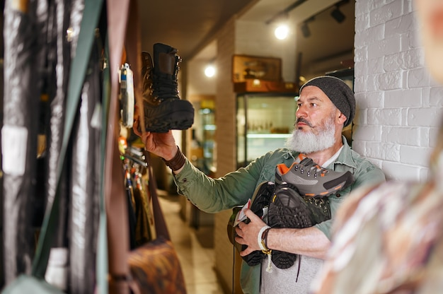 Bearded male hunter choosing boots in gun store