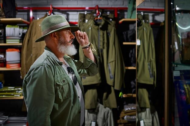 Бородатый мужчина-охотник, выбирая шляпу в оружейном магазине. интерьер оружейного магазина, ассортимент винтовок и боеприпасов, выбор огнестрельного оружия, хобби и образ жизни.