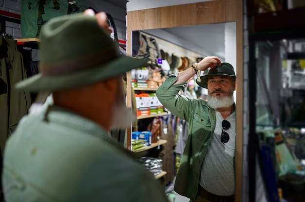 Бородатый мужчина-охотник выбирает шляпу в оружейном магазине