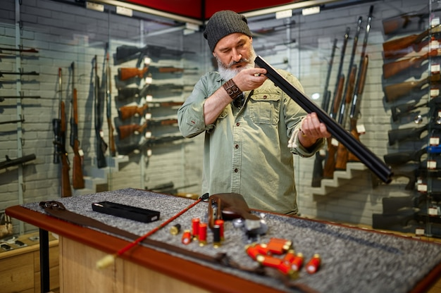 Бородатый мужчина-охотник чистит шомпол в оружейном магазине. интерьер оружейного магазина, ассортимент винтовок и боеприпасов, выбор огнестрельного оружия, увлечение стрельбой