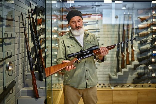 수염 난 남성 사냥꾼은 총기 가게에서 광학 시력이 있는 사냥용 소총을 들고 있습니다. 무기 상점 인테리어, 탄약 및 탄약 구색, 총기 선택, 사격 취미 및 라이프 스타일