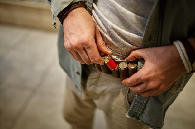 수염 난 남성 사냥꾼은 총기 가게에서 가죽 띠를 싣습니다. 무기 상점 인테리어, 소총 및 탄약 구색, 총기 선택, 사격 취미 및 라이프 스타일