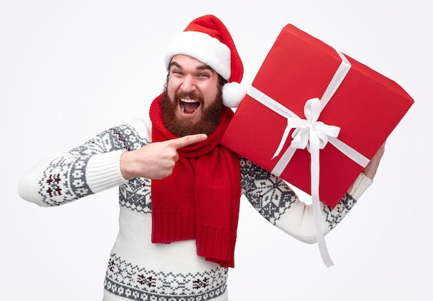 巨大なギフトボックスを指してクリスマス帽子のひげを生やした男性
