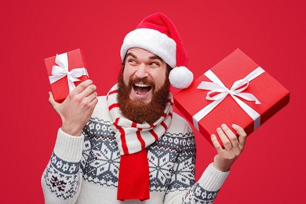 クリスマスプレゼントを受け取って叫んでサンタ帽子のひげを生やした男性