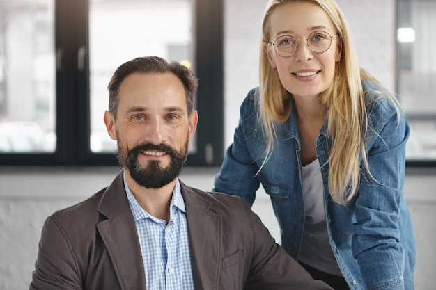 Bearded male manager in formal suit and his female assistant