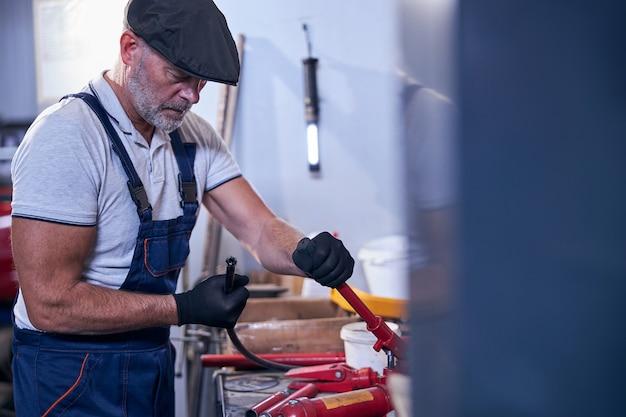 ガレージで働く帽子のひげを生やした男性の整備士