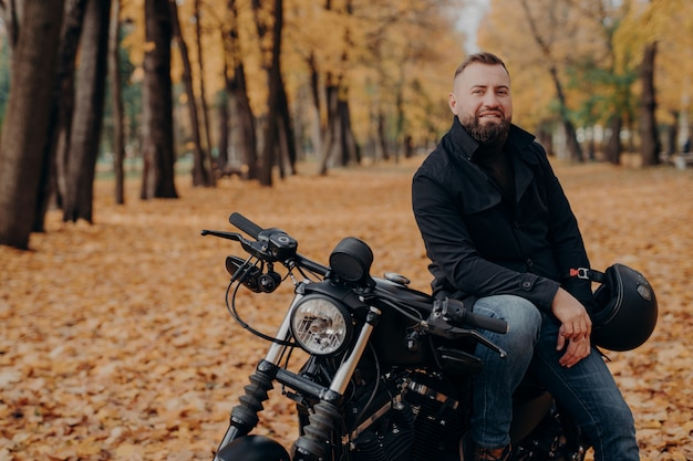 Bearded male motorcyclist rides black bike, holds helmet, has travel on his own transport