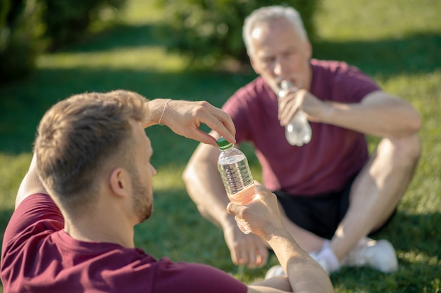 Bearded male opening bottle of water, grey-haired man drinking water, both sitting on grass