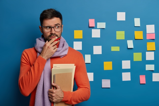 Bearded male organizing his tasks using sticky notes