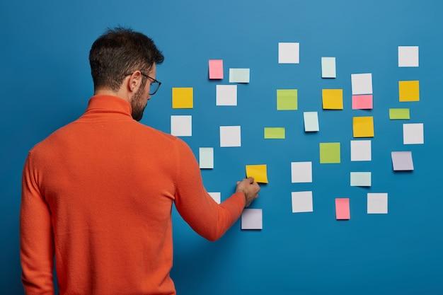 Maschio barbuto che organizza i suoi compiti utilizzando note adesive