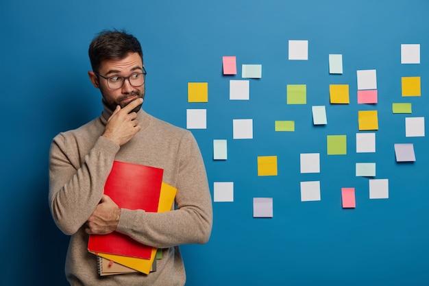 Бородатый мужчина организовывает свои задачи с помощью липких заметок