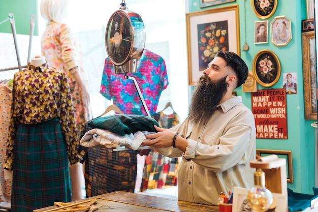ひげを生やした男性の所有者が彼の衣料品店で体重計の布の重量をチェック