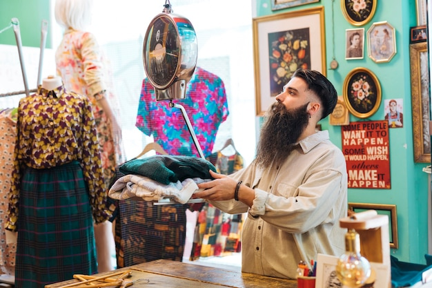 Bearded male owner checking fabric weight on scales at his clothing shop