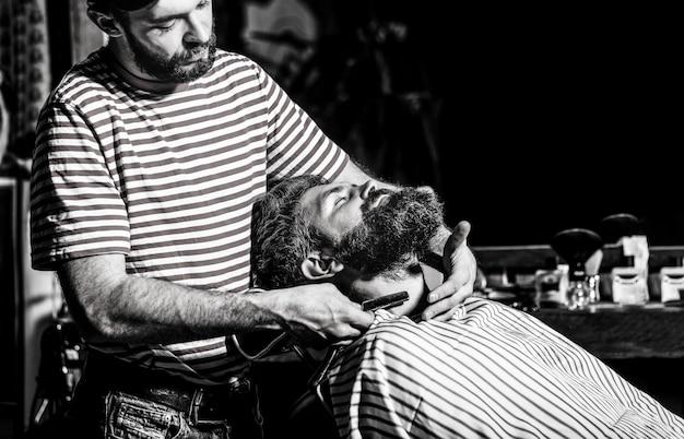 理髪店の肘掛け椅子に座っているひげを生やした男性が、美容師が危険なかみそりでひげを剃っている。理髪店でひげを生やした男を剃る理髪店。黒と白。