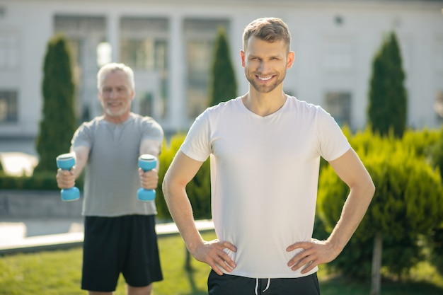 Бородатый мужчина улыбается, руки на бедрах, седой мужчина поднимает гантели сзади