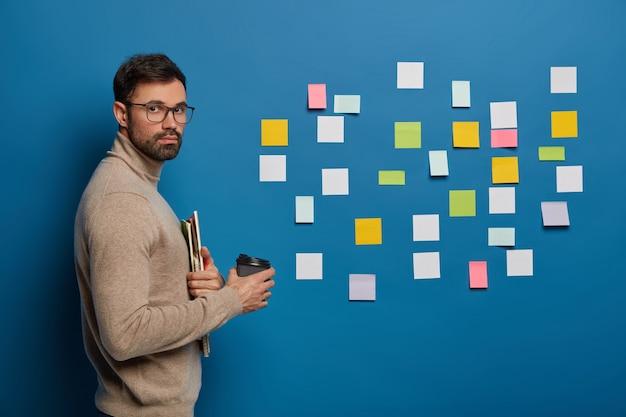 Бородатый студент мужского пола проводит перерыв на кофе в помещении, держит одноразовую чашку с горячим напитком, использует наклейки для запоминания новой информации