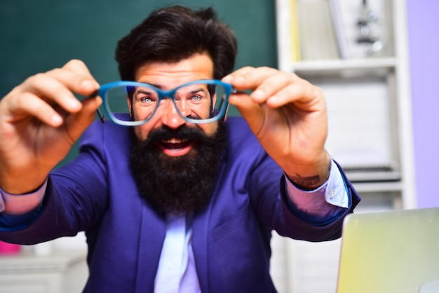 Bearded male student holds glasses happy university student near chalkboard in classroom funny male