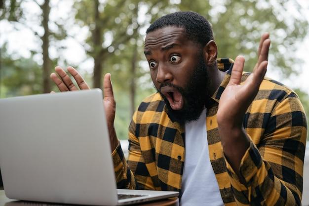 彼のラップトップで何かを見て驚いたひげを生やした男性