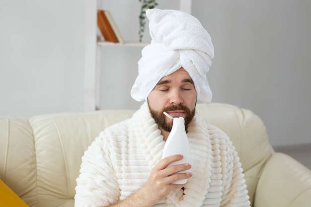 ボディローションクリームを塗って頭にタオルをかぶったひげを生やした男性。手持ちのローションクリームの匂いを嗅ぐと男の笑顔。男性のコンセプトのためのスパ、ボディ、スキンケア。