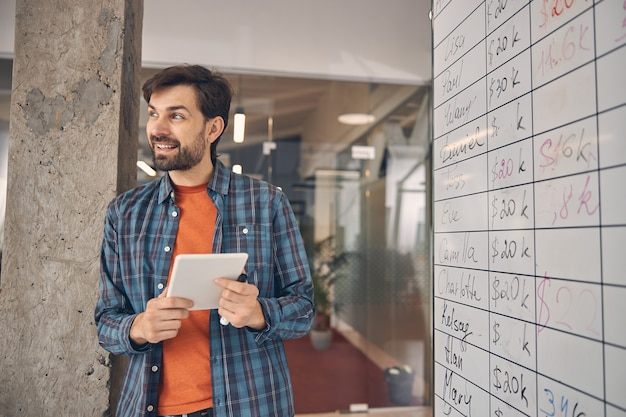 Bearded male worker looking away and smiling while holding electronic pad pc and standing near whiteboard in office