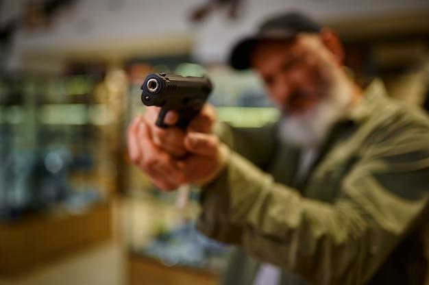 あごひげを生やした男は銃の店でピストルを目指しています。武器屋のインテリア、弾薬と弾薬の品揃え、銃器の選択、射撃の趣味とライフスタイル、護身術
