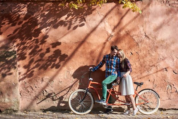 Бородатый мужчина и блондинка женщина, опираясь вместе на двойной тандем велосипед на фоне высокой красной старой потрескавшейся оштукатуренные стены.