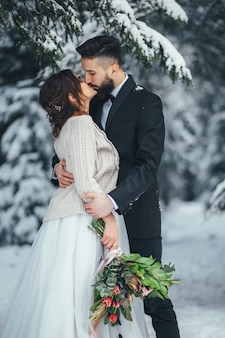 Bearded man and his lovely bride pose on the snow in a magic winter forest